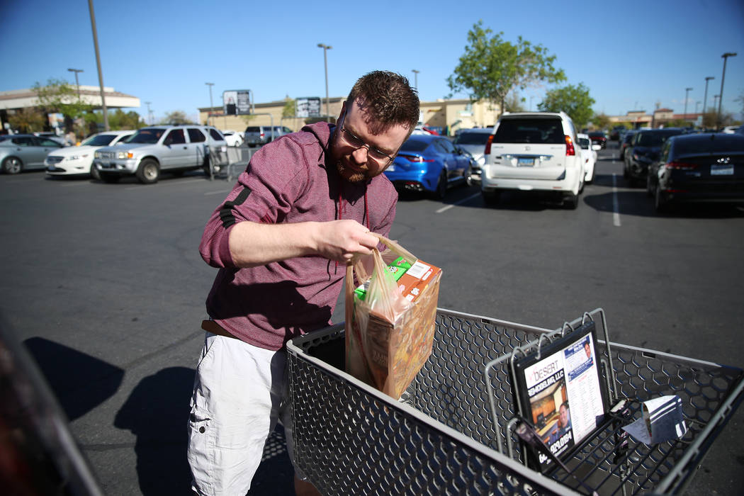 Mark Schoenfeldt of Las Vegas loads his car with groceries after shopping at Smith's, 10600 Sou ...