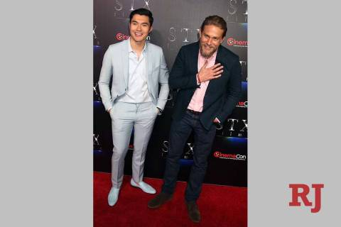 Actors Henry Golding, left, and Charlie Hunnam arrive at CinemaCon red carpet at The Colosseum ...