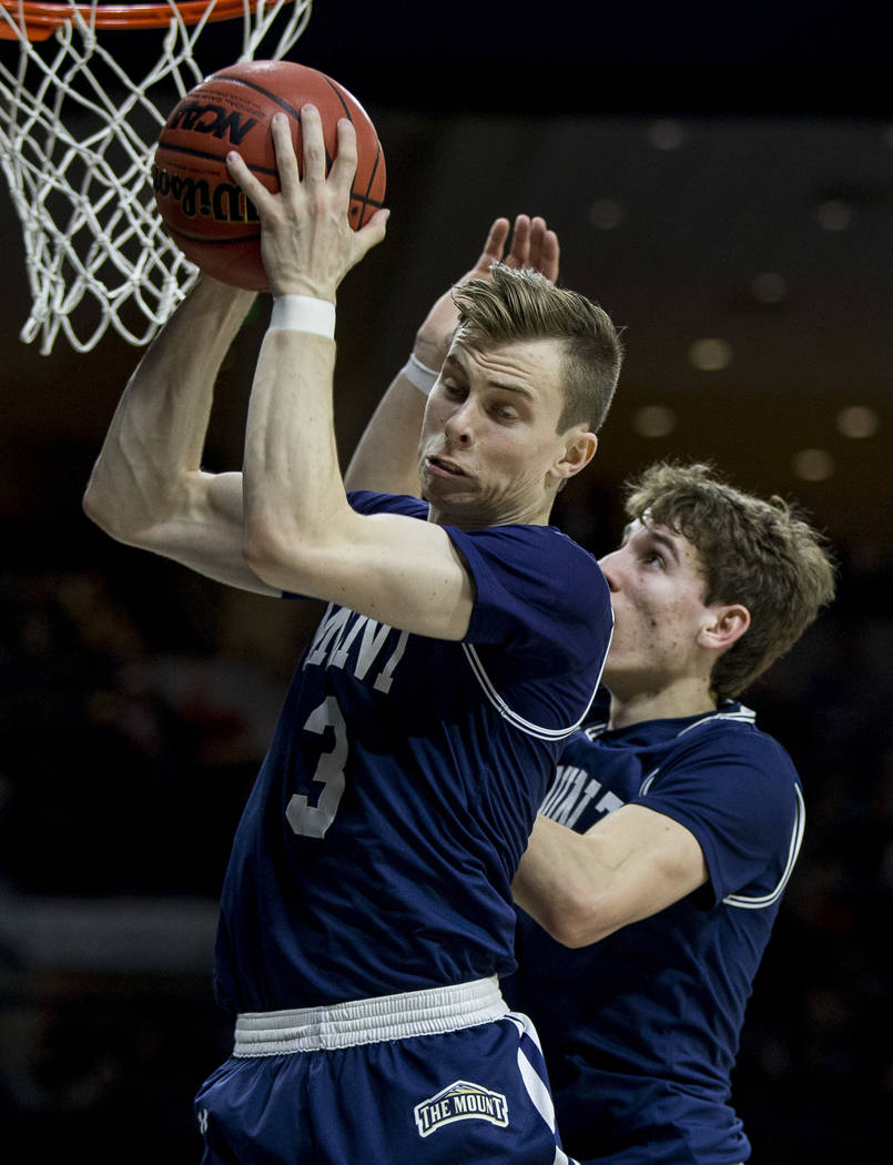 Mount St. Mary's Jonah Antonio (3) grabs a rebound in front of teammate Bobby Planutis during t ...
