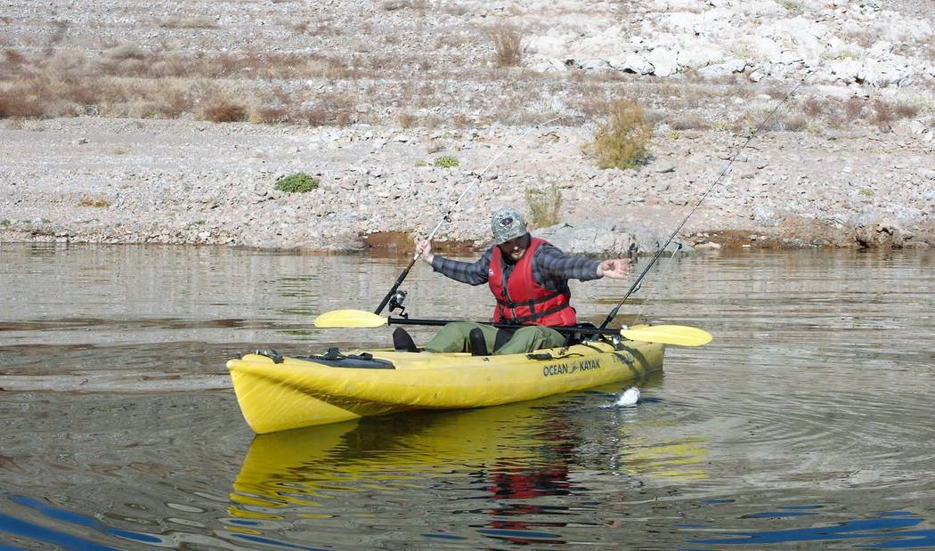 Hyrum Nielsen pulls in a Lake Mead catfish while fishing from a kayak. Notice the simple riggin ...