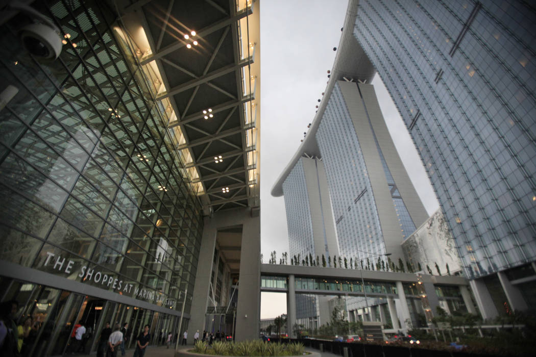 People walk near the facade of the Marina Bay Sands integrated resort, June 23, 2010. (Wong Ma ...