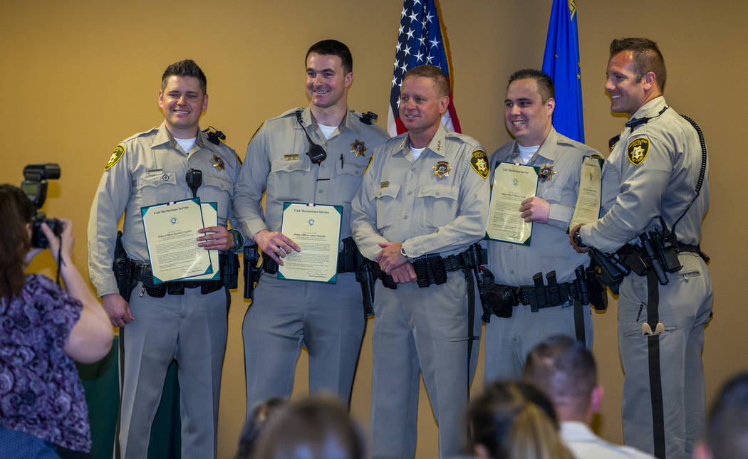 Officers receive a lifesaving and unit meritorious award from Undersheriff Kevin McMahill durin ...