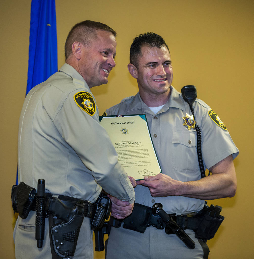 Undersheriff Kevin McMahill presents Detective John Johnson with a meritorious award during a M ...