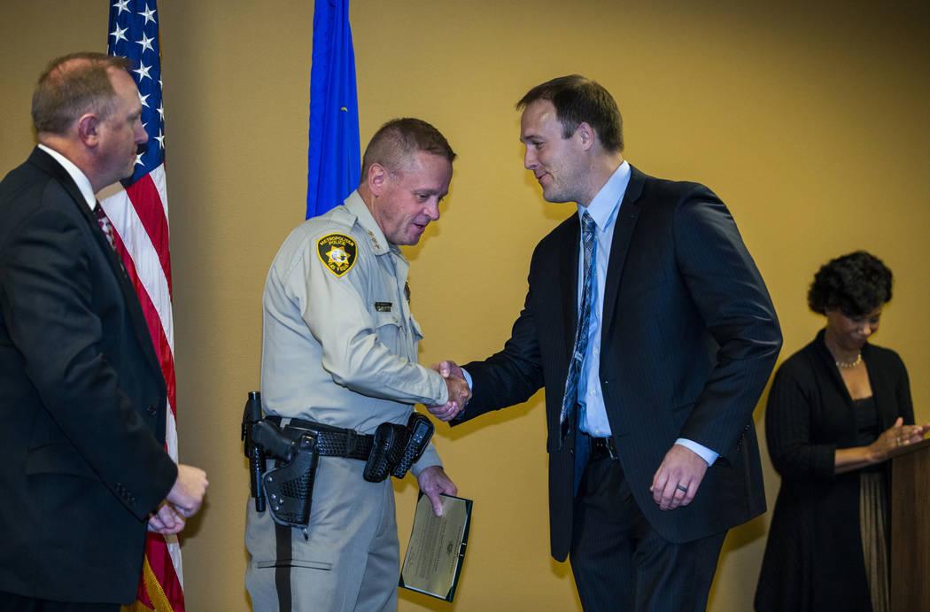 Undersheriff Kevin McMahill presents FBI Special Agent Daniel Coxon with a meritorious award du ...