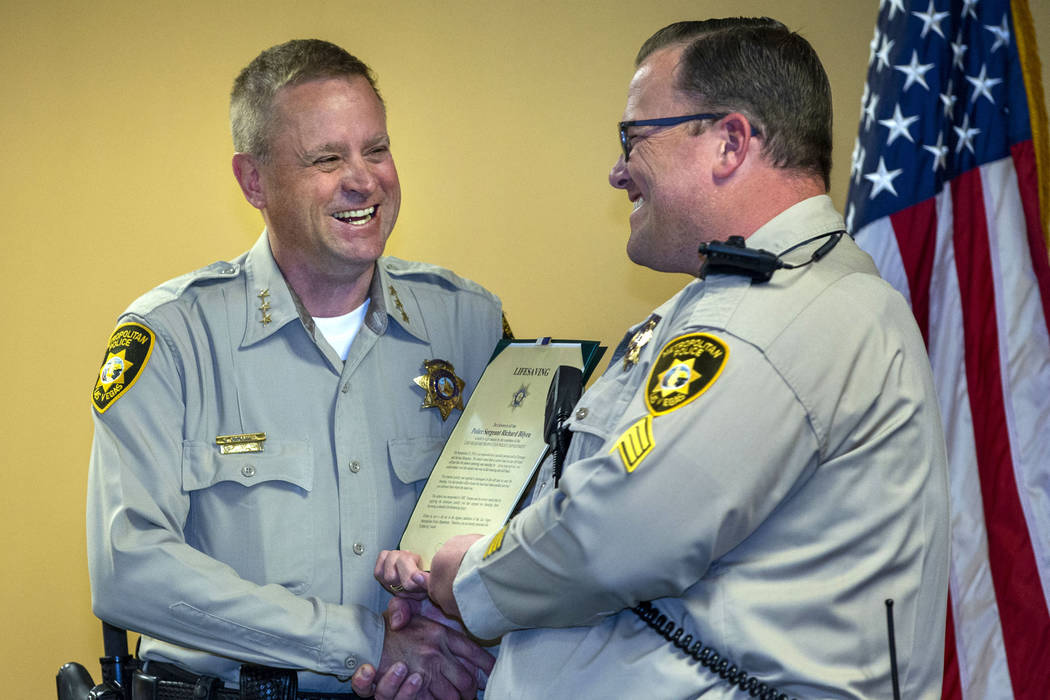 Undersheriff Kevin McMahill presents Sgt. Richard Bilyeu with a lifesaving award during a Metro ...