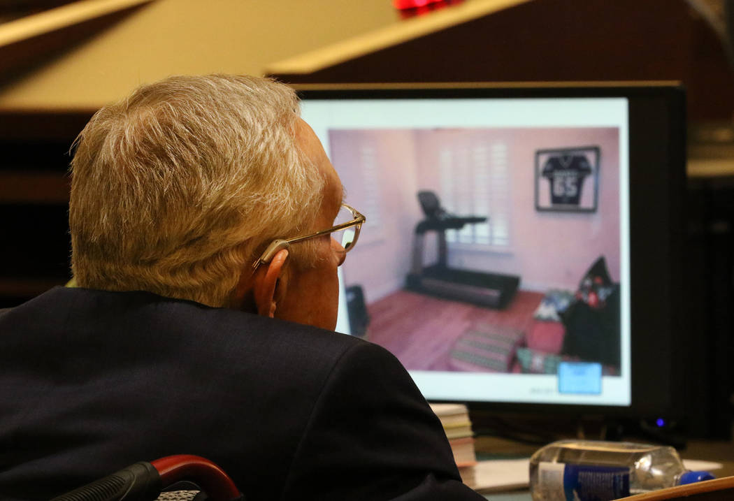 Former U.S. senator Harry Reid watches a photograph of his exercise room, that was displayed du ...