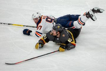Edmonton Oilers center Connor McDavid (97) lands on top of Vegas Golden Knights right wing Mark ...