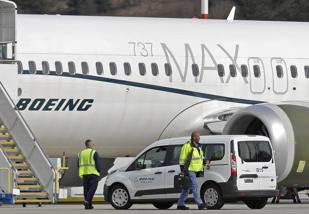 Workers walk next to a Boeing 737 MAX 8 airplane parked at Boeing Field, in Seattle on March 14 ...