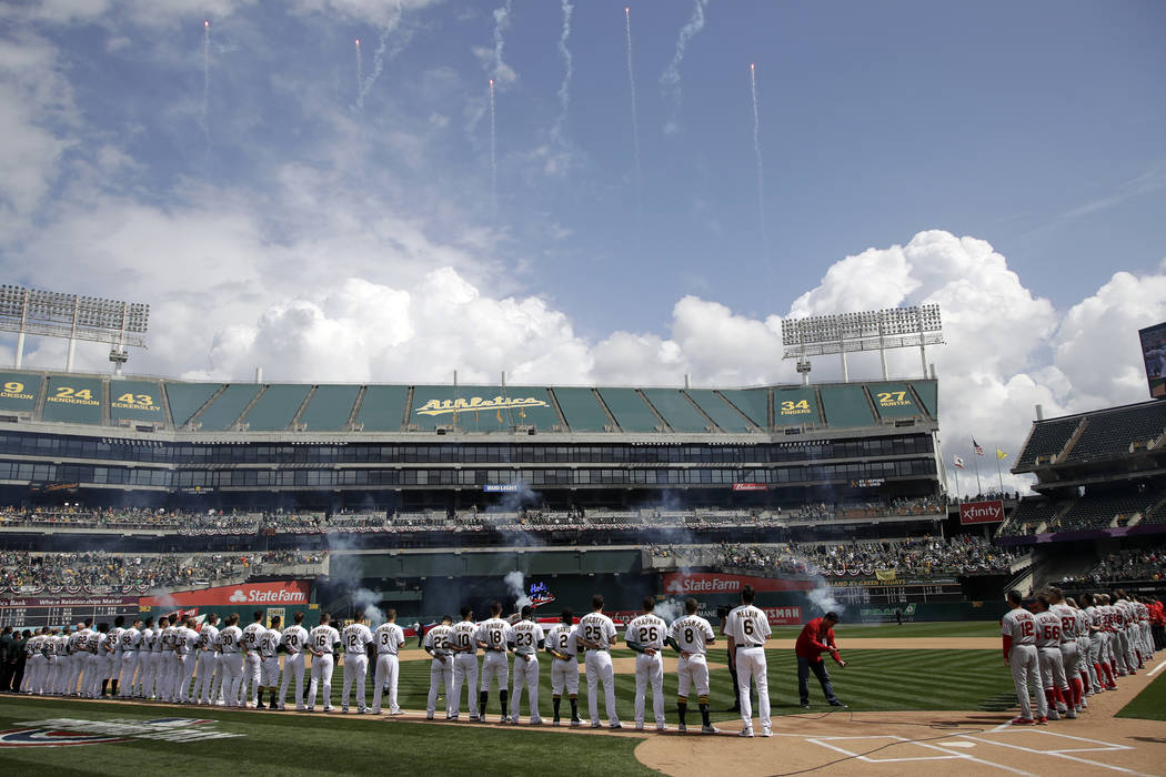 The Oakland Athletics and Los Angeles Angels watch fireworks during the national anthem prior t ...