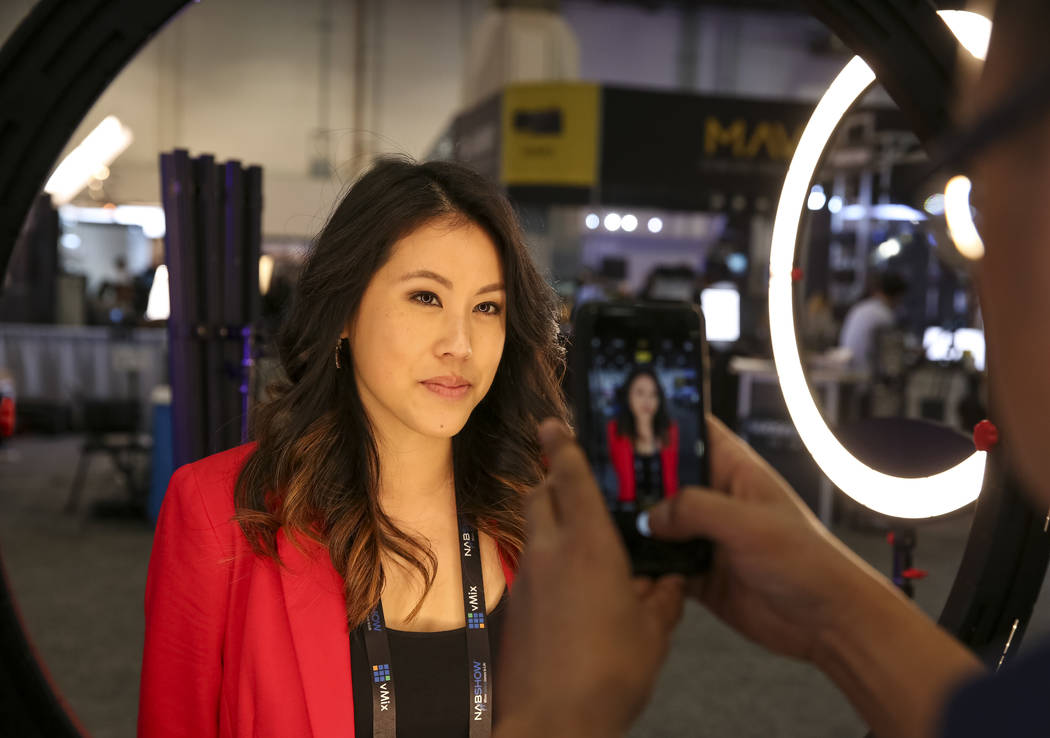 Nicki Sun of Los Angeles poses under an LED ring light at the Came-Tv booth during the final da ...