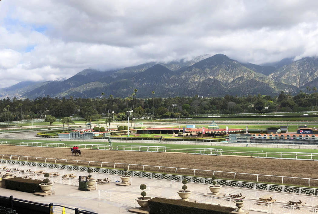 A few horses and riders are seen on the track while members of the California Horse Racing Boar ...