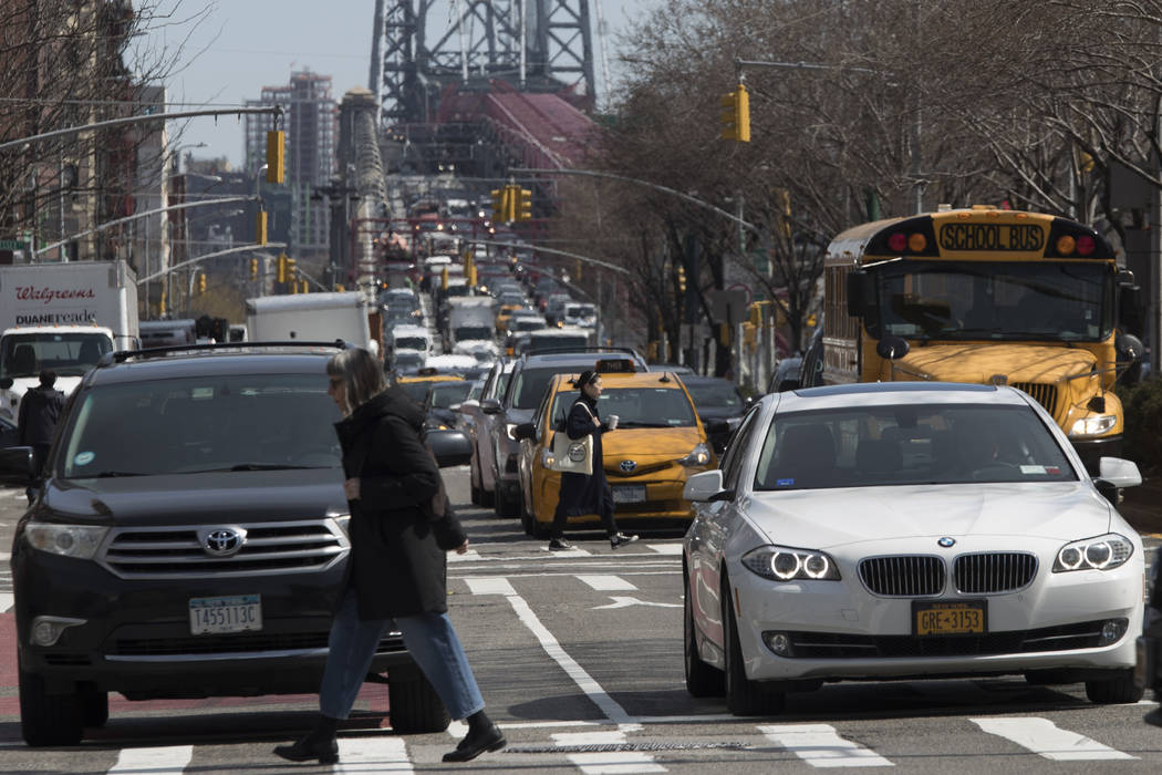 In this March 28, 2019 photo, pedestrians cross Delancey Street as traffic is seen making its w ...