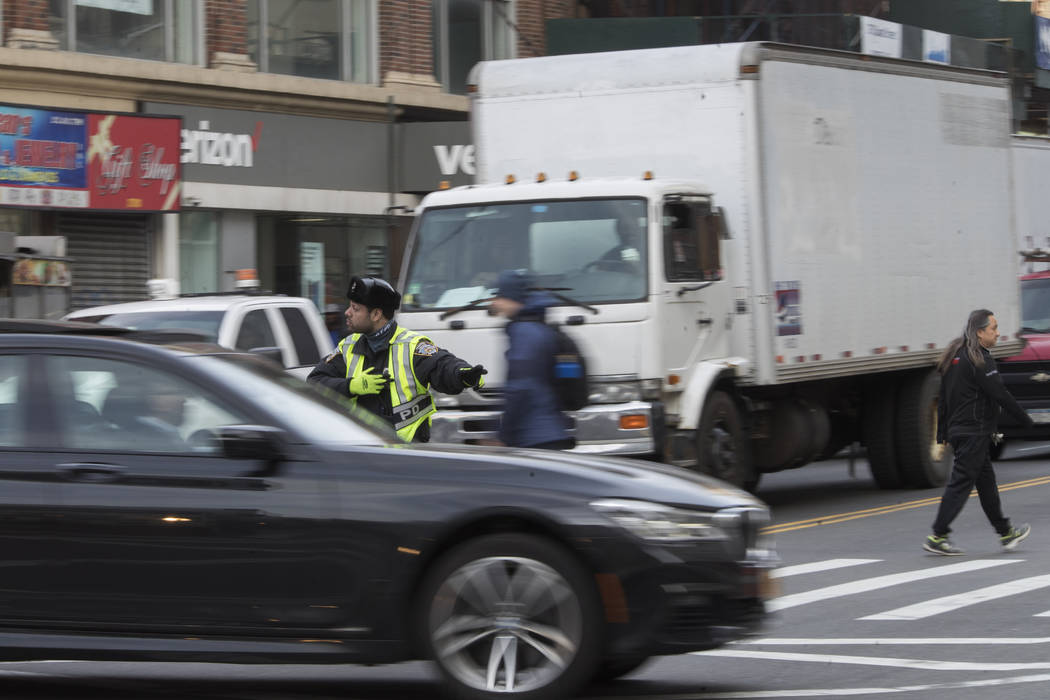 In this March 28, 2019 photo, a police officer directs rush hour traffic on Canal Street in New ...