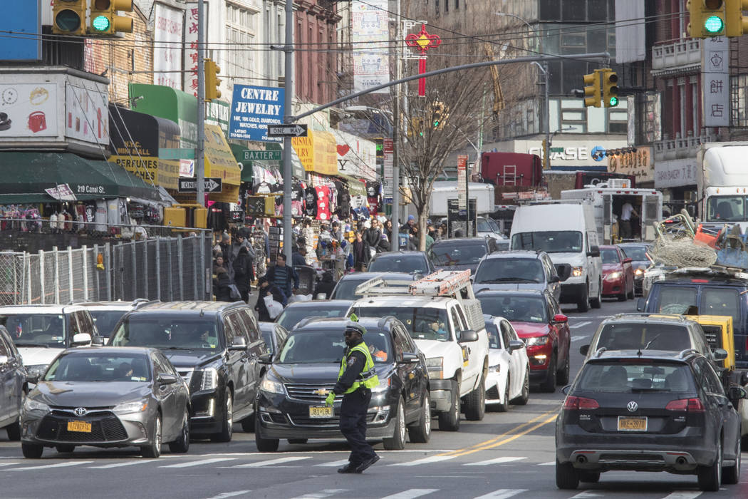 In this May 28, 2019 photo, a police officer directs rush hour traffic on Canal Street in New Y ...