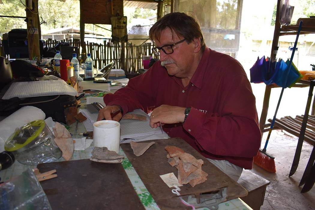 UNLV anthropologist Arlen Chase examines pieces of pottery at the Maya ruin site of Caracol in ...