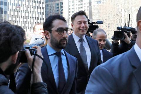 Tesla CEO Elon Musk, center, arrives at Manhattan Federal Court, in New York, Thursday, April 4 ...