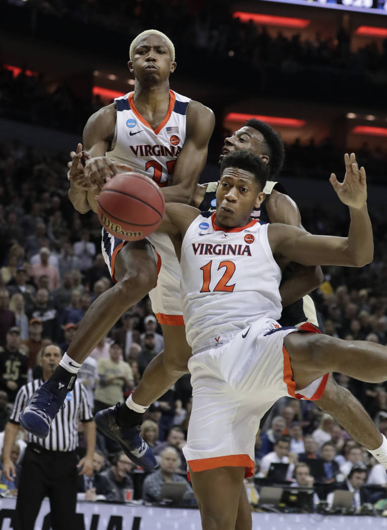 Purdue's Aaron Wheeler, rear, battles for a rebound against Virginia's Mamadi Diakite, left, an ...