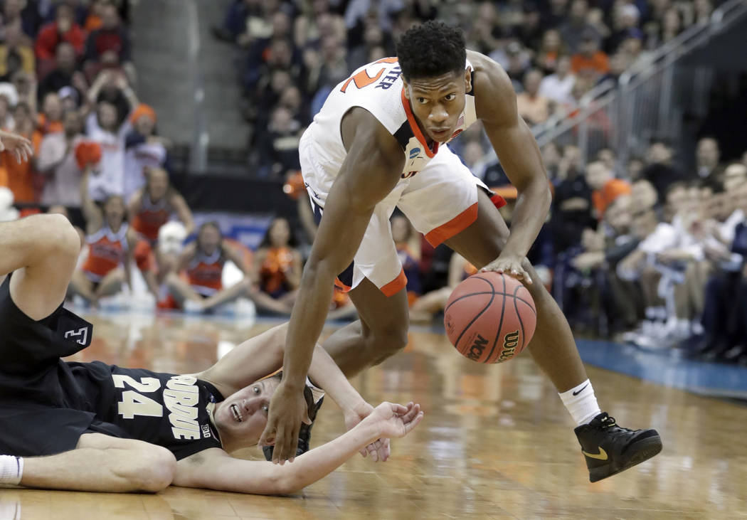 FILE - In this March 30, 2019, file photo, Virginia's De'Andre Hunter dribbles past Purdue's Gr ...