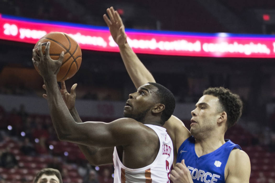 UNLV sophomore guard Amauri Hardy (3) drives past Air Force freshman guard Zach Couper (2) in t ...