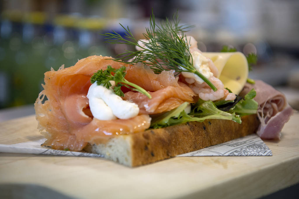 A smoked salmon sandwich is prepared before serving to a customer at Saga Pastry + Sandwich in ...