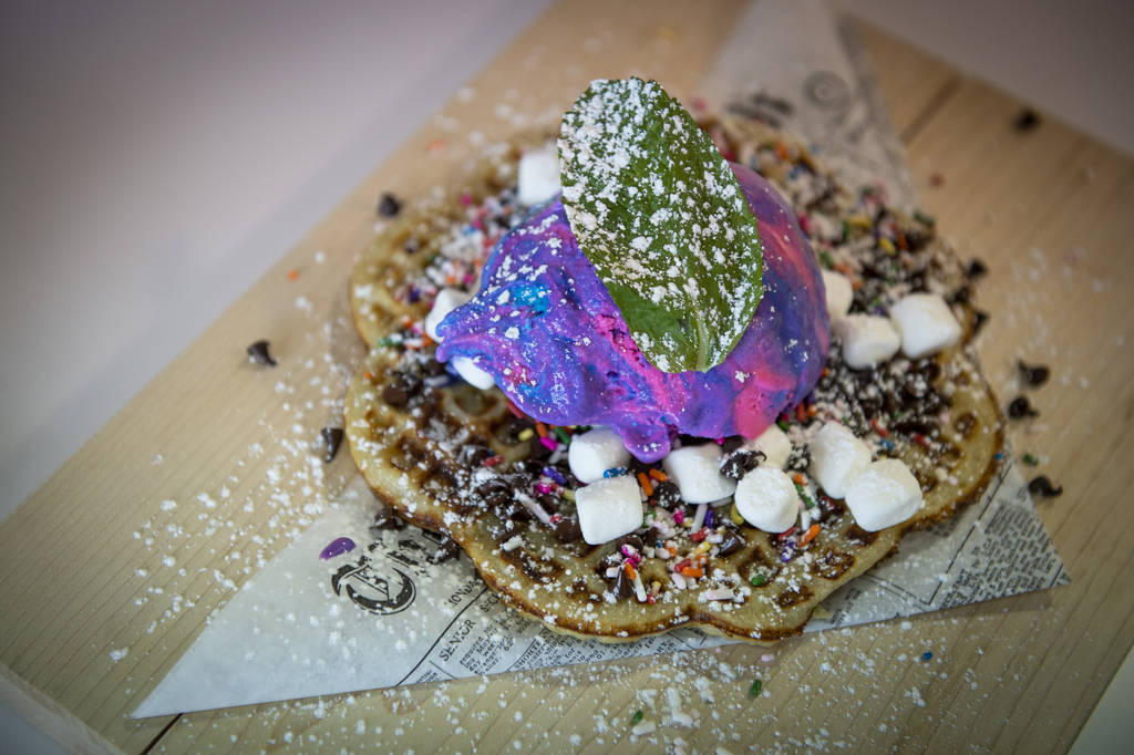 A nordic waffle with ice cream, Nutella, sprinkles, chocolate chips and marshmallows is served ...