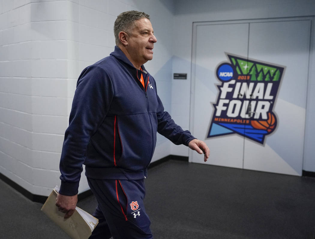 Auburn head coach Bruce Pearl walks to a news conference after a practice session for the semif ...