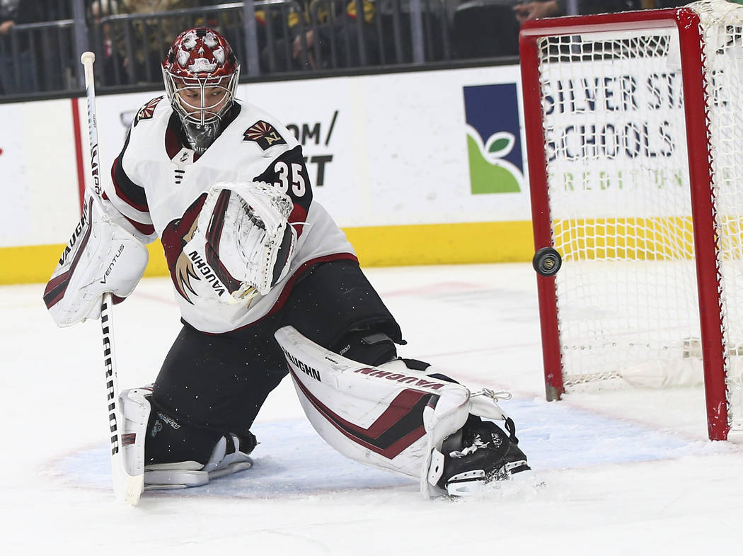 A shot flies by Arizona Coyotes goaltender Darcy Kuemper (35) during the first period of an NHL ...