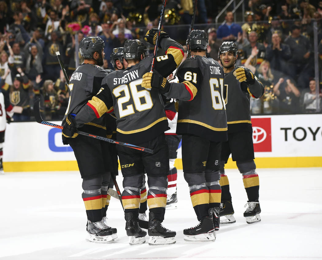 Golden Knights players celebrate a goal by Mark Stone (61) during the first period of an NHL ho ...