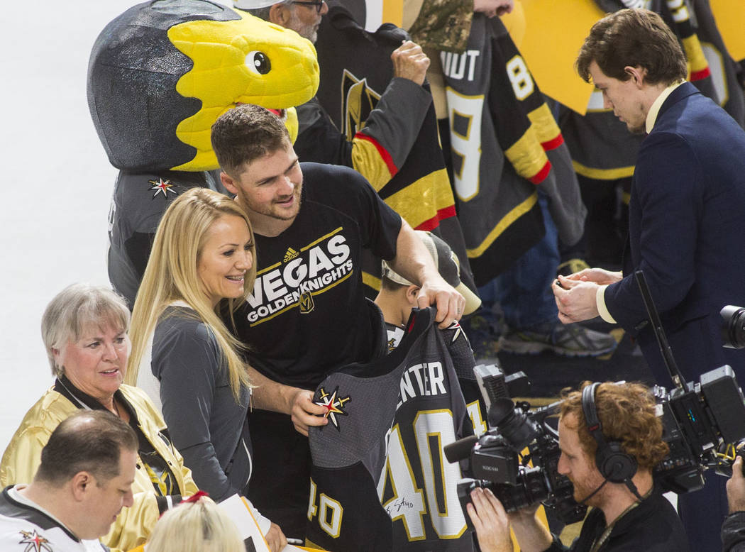 Golden Knights center Ryan Carpenter (40) poses with a lucky fan while joining players in signi ...