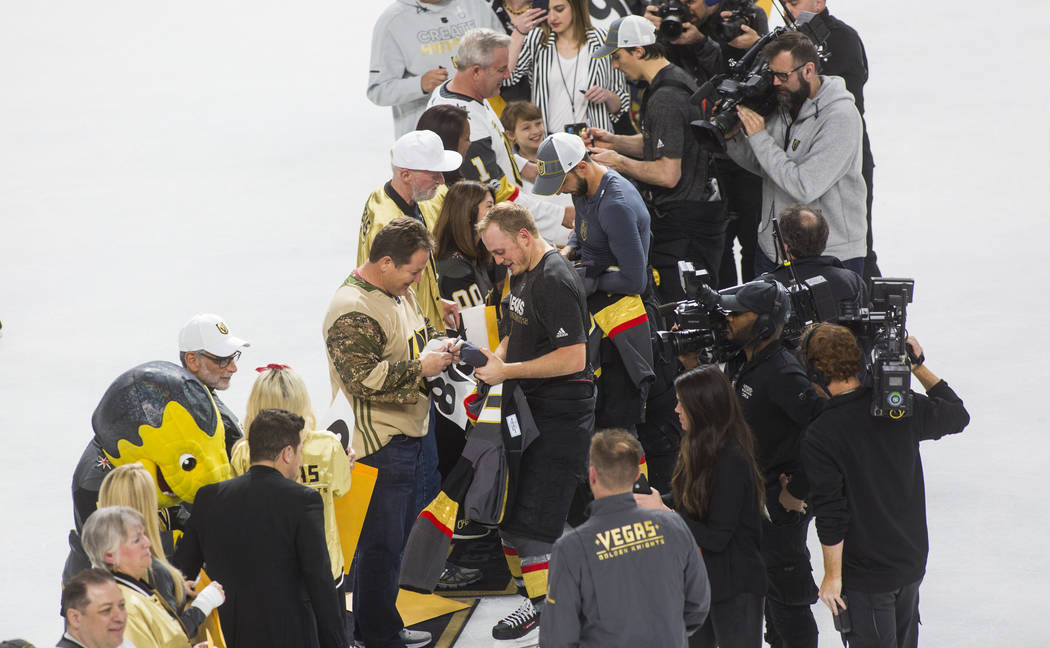 Golden Knights defenseman Nate Schmidt, center left, joins other players in signing and giving ...