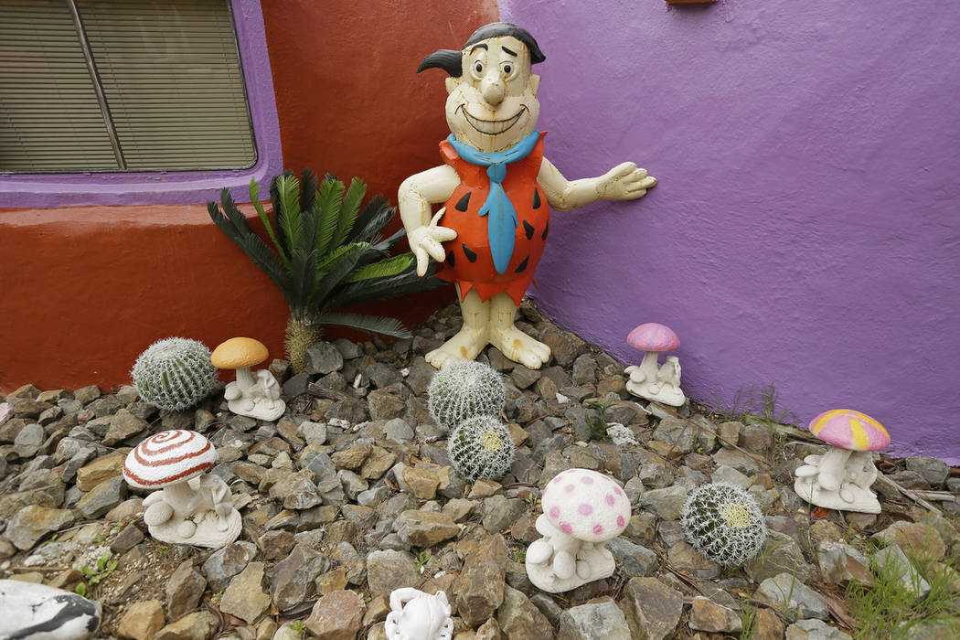 In this photo taken Monday, April 1, 2019, are figurines of Fred Flintstone standing among mush ...