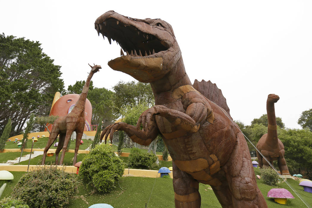 In this photo taken Monday, April 1, 2019, dinosaurs and other figurines stand in the backyard ...