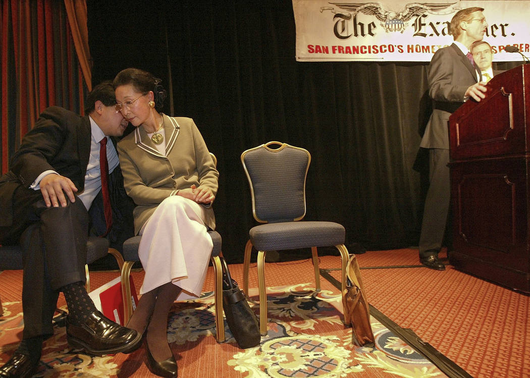 In this Feb. 19, 2004, photo, James Fang, left, talks with his mother, Florence Fang, as presid ...