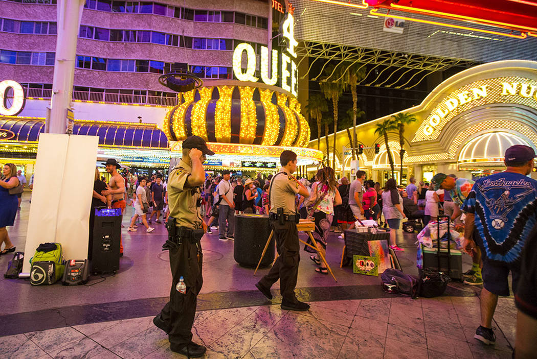 Security officers patrol along the Fremont Street Experience in downtown Las Vegas on Thursday, ...