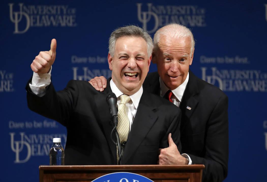 Former Vice President Joe Biden, right, embraces University of Delaware President Dennis Assani ...
