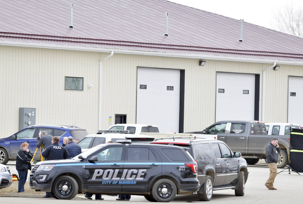 Mandan, N.D. Police Deputy Chief Lori Flaten, left, and other law enforcement personnel stand o ...