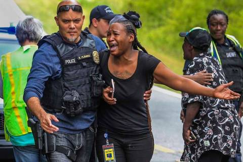 A woman believed to be related to ones involved in a hostage situation reacts as law enforcemen ...