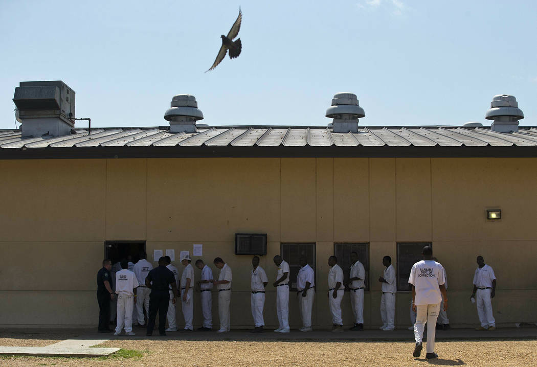 Prisoners stand in a lunch line during a prison tour at Elmore Correctional Facility in Elmore, ...