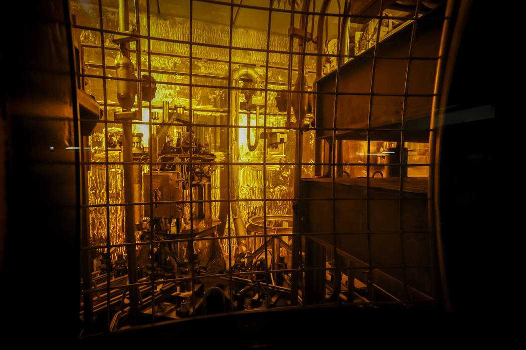 Seen through thick protective glass, shows the area where workers sand-blast the large stainles ...