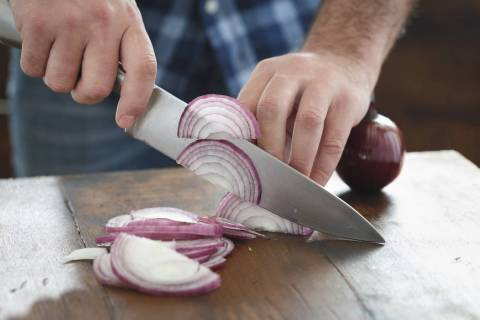A man chops onions on a table. (Getty Images)