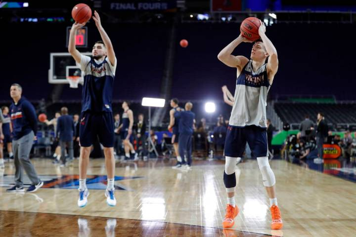 Virginia's Ty Jerome, left, and Kyle Guy shoot during a practice session for the semifinals of ...