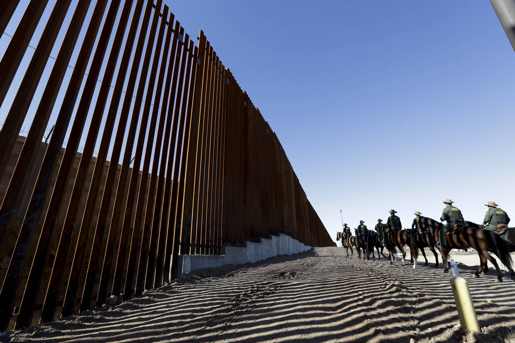 Mounted Border Patrol agents ride along a newly fortified border wall structure on Oct. 26, 201 ...