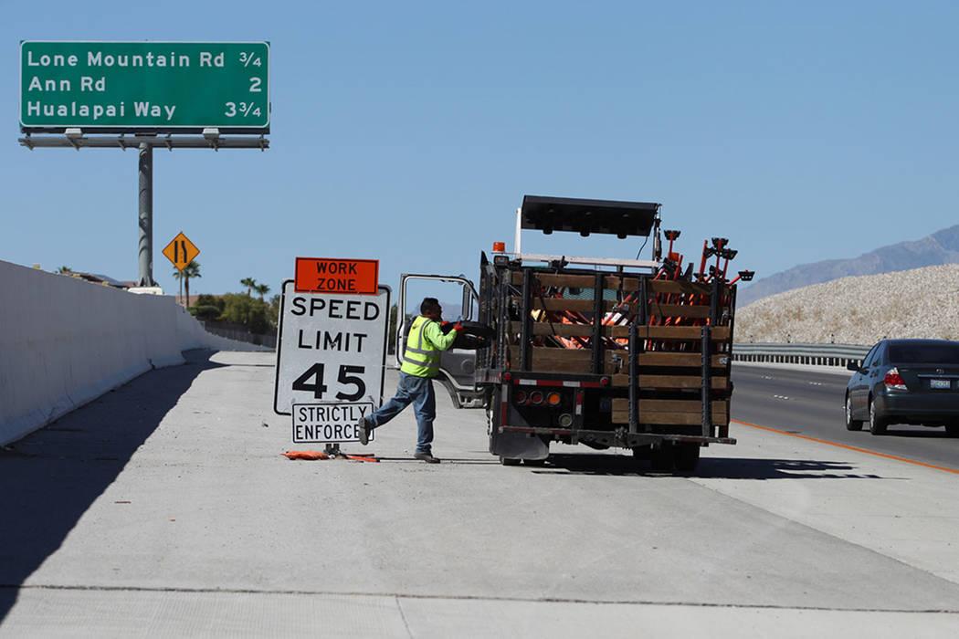 Cesar Escobar, traffic control supervisor for Las Vegas Paving Corporation, removes a work zone ...