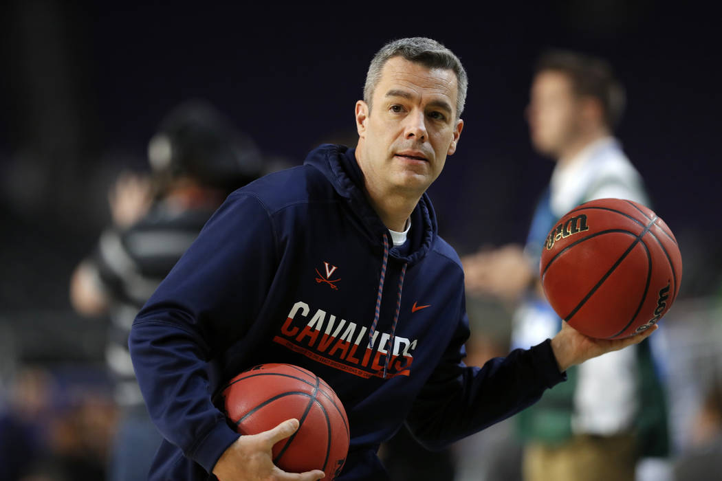 Virginia head coach Tony Bennett passes the ball during a practice session for the semifinals o ...
