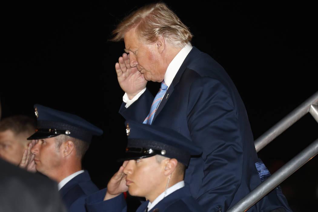 President Donald Trump salutes as he arrives at McCarran International Airport in Las Vegas Fri ...