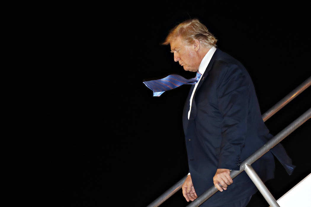President Donald Trump's tie is blown in the wind as he walks down the stairs of Air Force One ...