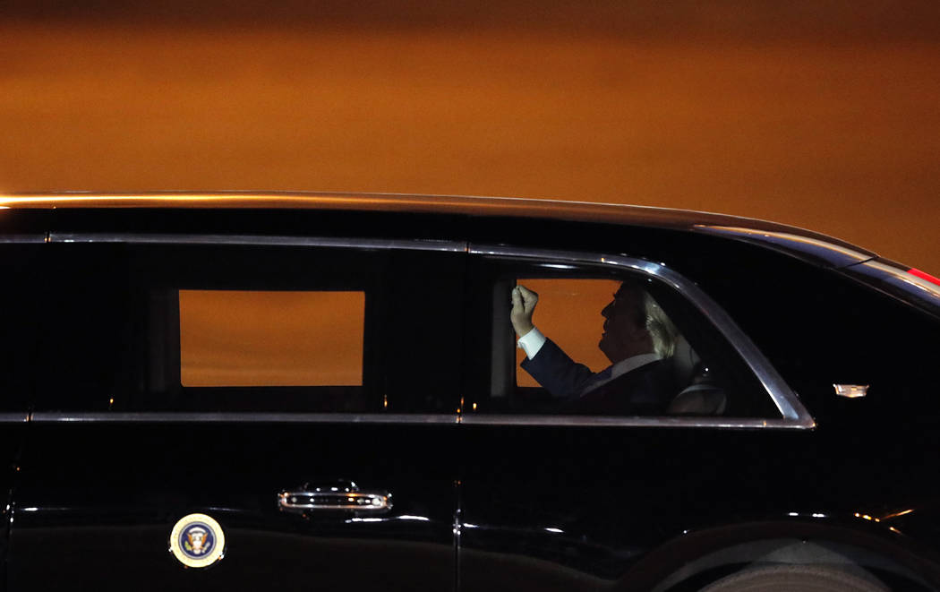 President Donald Trump leaves in the presidential limousine after arriving at McCarran Internat ...
