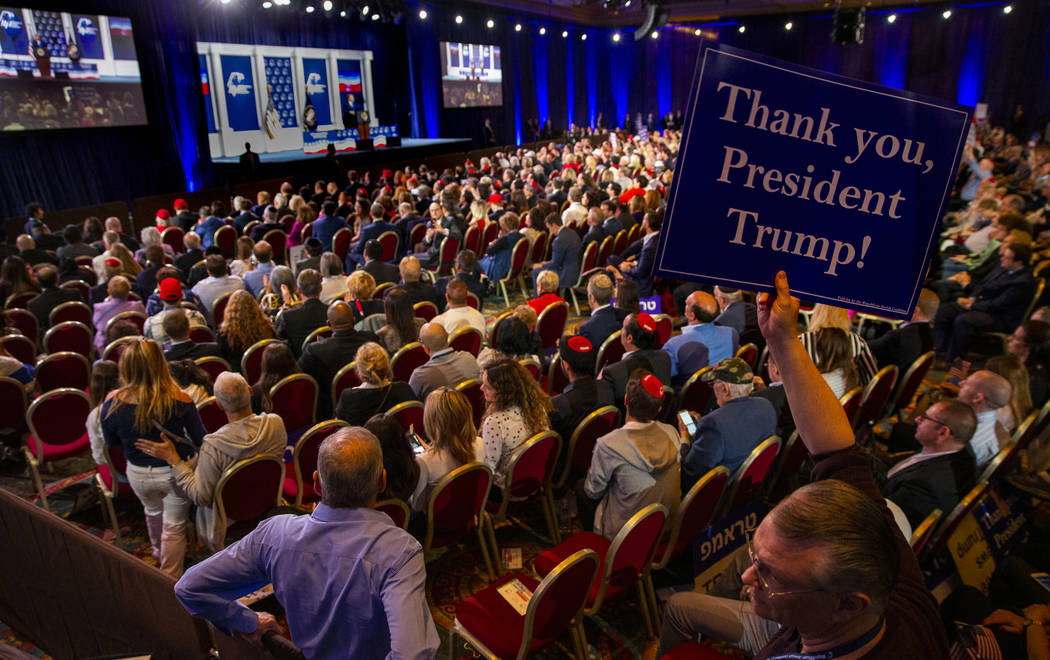 An attendee holds up a sign as President Donald J. Trump addresses the Republican Jewish Coalit ...