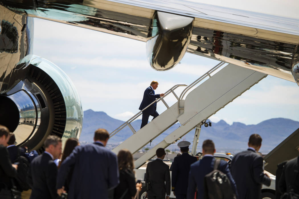 President Donald J. Trump climbs the stairs as he readies to depart from McCarran International ...