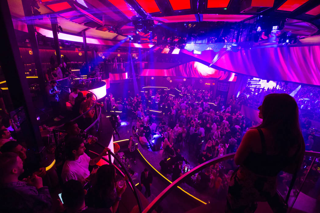 Attendees take in views of the nightclub from the mezzanine during the grand opening weekend of ...